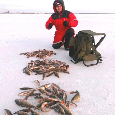 Ice fishing on the frozen sea in Oulu, Finland