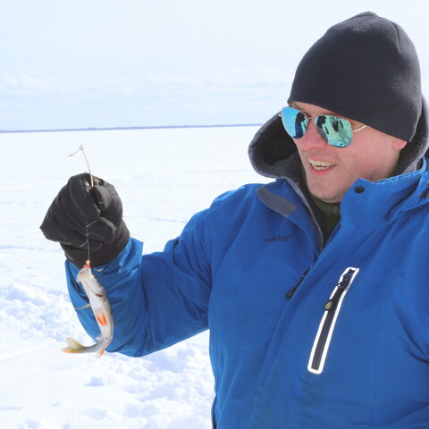 Ice fishing on the frozen sea in Oulu, Finland